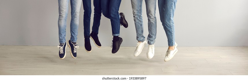 Group of young people in blue jeans and black and white sneakers feeling free and happy and jumping. Cropped low section indoor shot of men and women's legs and feet in mid air. Shoe fashion concept