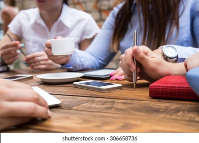 Group of young people at cafe table Conceptual image of people hands around vintage natural wood desk drinking coffee using pen, telephones and other gadgets at open space terrace