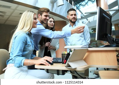 Group of young people in casual wear sitting at the office desk and discussing something while looking at PC together.
