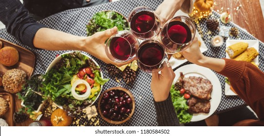 Group of young people celebrating Christmas thanksgiving party dinner with clinking glass of wine, top view