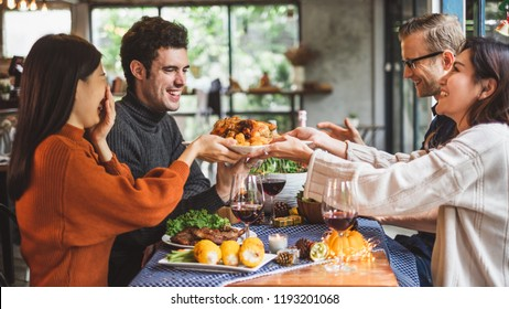 Group of young people celebrating Christmas party dinner with clinking glass of wine, Christmas and thanksgiving concept