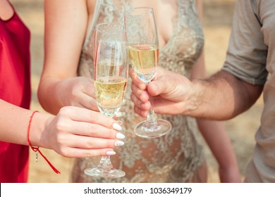 a group of young people celebrating with glasses of champagne on the beach. Glass glasses with sparkling wine in the hands of women and men on vacation
