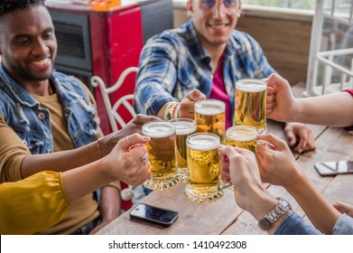 Group of young people celebrating toasting with beer at the pub