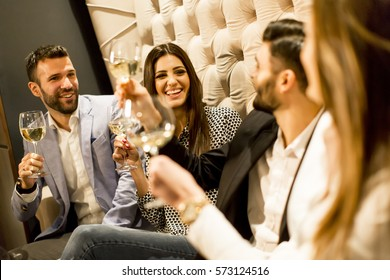 Group of young people celebrating and toasting with white wine