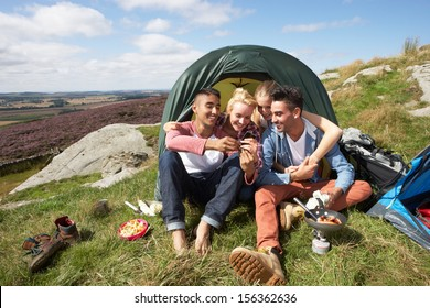 Group Of Young People Checking Mobile Phone On Camping Trip
