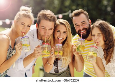 Group of young people cheering and having fun outdoors with drinks