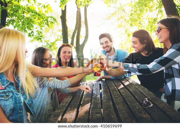Group of young people cheering, having fun outdoors