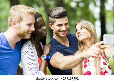 Group of young people and couples taking selfies in nature and smiling