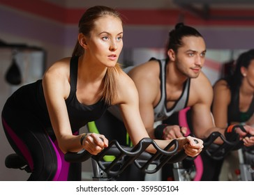 Group of young people cycling in class in gym