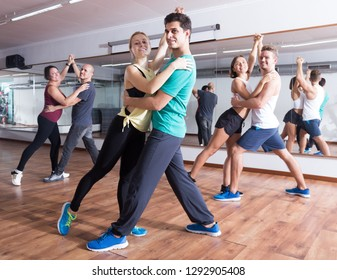 Group of young people dancing salsa together in dance studio