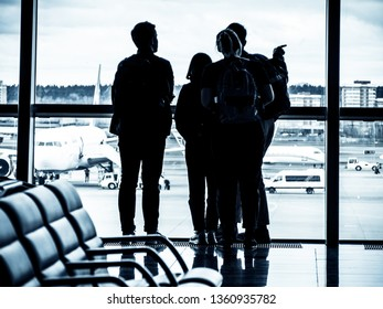 A group of young people at a departure lounge of a modern airport