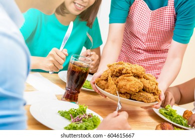 Group of young people at dining table ready to eat fried chicken being served by the waiter in restaurant