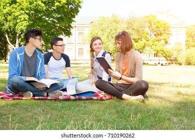 Group of young people discuss and talk. Students sitting on a clearing in the campus.
