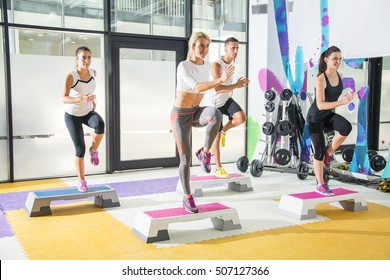 Group of young people doing exercises on stepper in a gym.