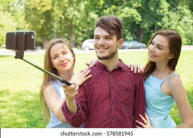 Group of young people are doing a self portrait to your mobile phone. A young man and two girls with pictures of the phone.