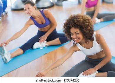 Group of young people doing stretching exercises in the fitness studio