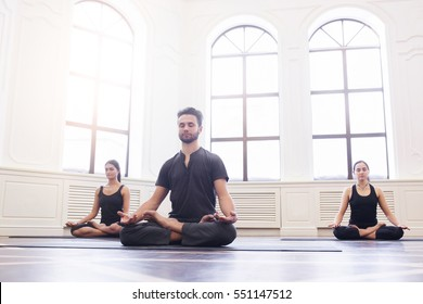 Group of young people doing yoga lotus pose in the class with windows. Fitness, sport, training and yoga lifestyle concept.