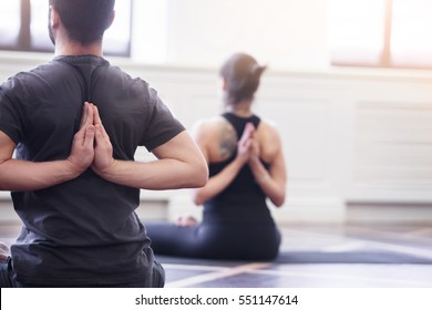 Group of young people doing yoga lotus pose in the class with windows. Fitness, sport, training and yoga lifestyle concept, back view.
