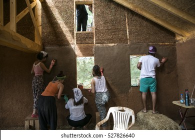 A group of young people earth plastering the wall of house.