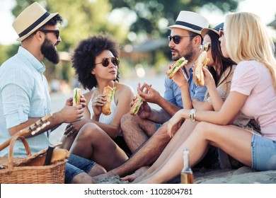 Group of young people eating sandwiches during picnic on beach.