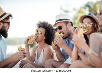 Group of young people eating sandwiches during picnic on the beach.