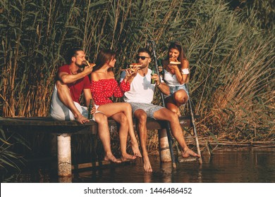 Group of young people eats pizza and drinking beer on a dock by the river during the summer sunny day