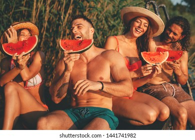 Group of young people eats watermelon on a dock by the river during the summer sunny day
