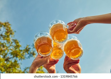 Group of young people enjoying and cheering beer outdoors.