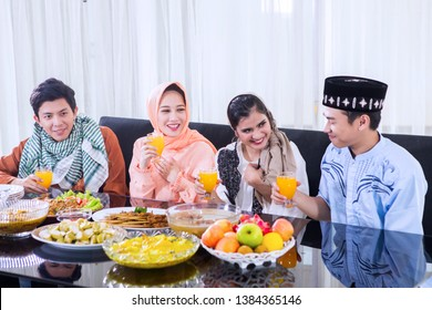 Group of young people enjoying orange juice during break the fast together in the dining room. Shot at home