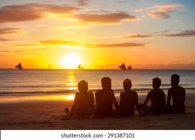 group of young  people, friends, team sitting  together on beach, sunset sky