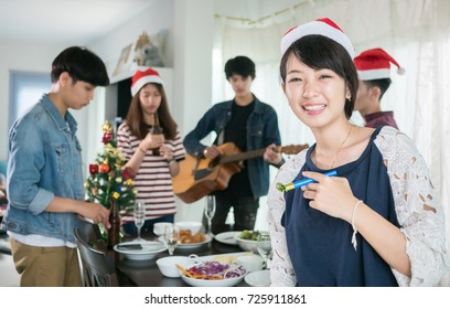 group of young people friendship eating together for Christmas party. Asian men and women smiling and happiness in Christmas food event celebration.