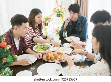Group of young people friendship eating together for Christmas party. Asian men and women happiness in Christmas food event celebration.