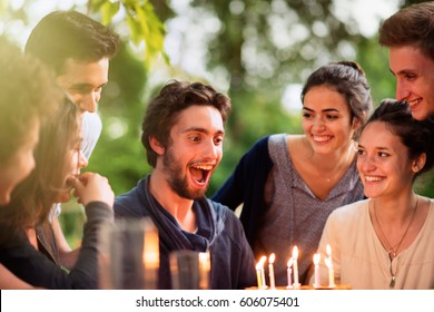 A group of young people gathered on a terrace in a garden to celebrate the birthday of one of their friends. A young man is blowing candles on the cake. Shot with flare