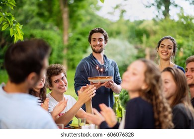 A group of young people gathered on a terrace to celebrate the birthday of one of their friends. A young man holding a cake with candles on it