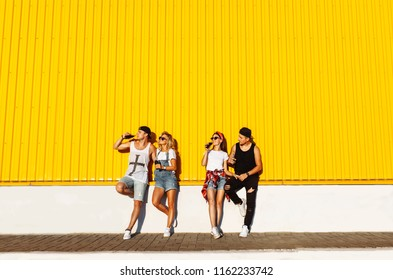 a group of young people with glass bottles with a drink stand near the supermarket, on a yellow background, friends come off in full, cheerful mood, Sunny day, Lifestyl concept