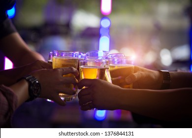 Group of  young people hands toasting and cheering aperitif beers half pint