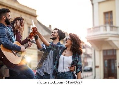 Group of young people hangout at the city street.They toasting with beer and playing guitar.