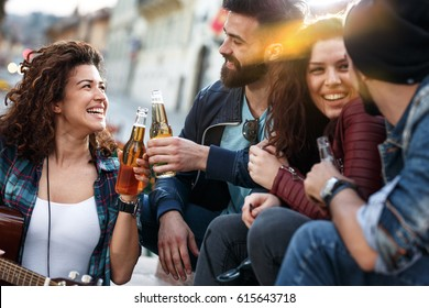 Group of young people hangout  on street in downtown.They sitting  on stairs,drinking and playing guitar.