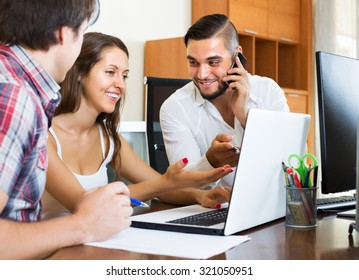 Group of young people have fun while watching something on laptop