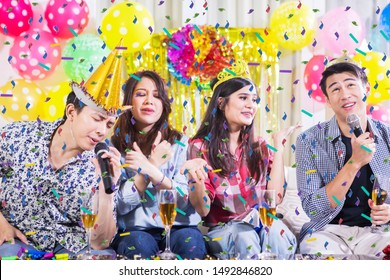 Group of young people having a birthday party while singing together