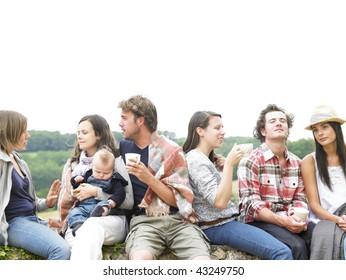 Group of young people having coffee outside in the morning, with one woman holding a baby. Horizontal.