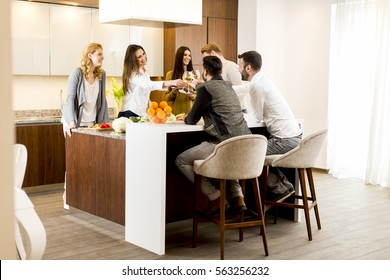 Group of young people having dinner and drinking wine in the modern kitchen