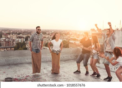 Group of young people having fun at summertime rooftop party, cheering for their contestants in a sack race