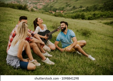 Group of young people having fun on a trip in nature on mountain