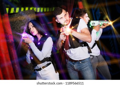 Group of young people having fun on dark lasertag arena in colorful beams of laser guns