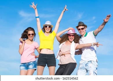 Group of young people having fun on a blue summer sky
