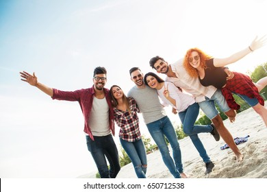 Group of young people having fun outdoors on the beach