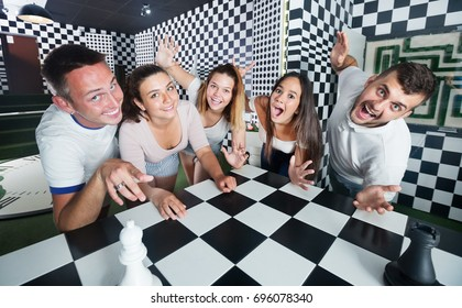 Group of young people having fun in an escape room stylized under a chessboard