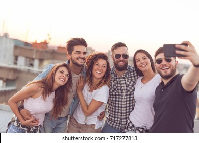 Group of young people having fun at a rooftop party, taking selfie. Focus on the people in the middle