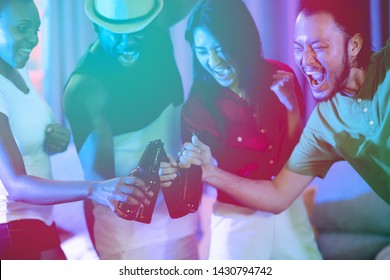Group of young people having a house party together. African american, Asian man and woman. Enojy getting drunk together. Mix race party concept. With light leaks.